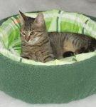 Кот в двойной лежанке, где наружная часть — из зелёного флиса, а внутренняя — из светлого хлопка