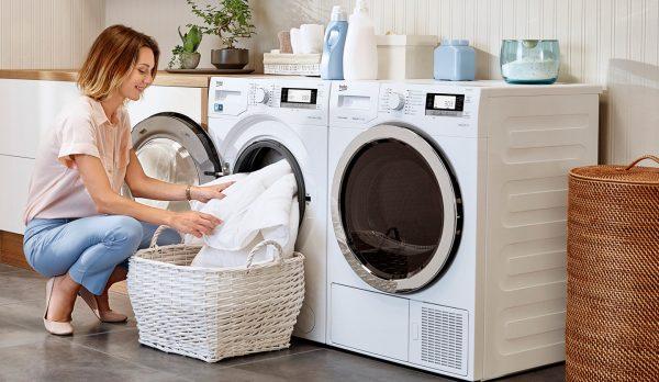 Женщина достаёт бельё из стиральной машинки