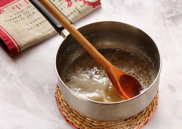 Кипящая жидкость в металлической кастрюле с деревянной ложкой