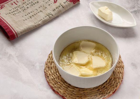 Кусочки сливочного масла в миске с сахарным сиропом