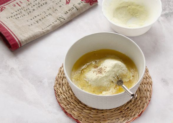 Сухое молоко и измельчённый кардамон в миске с сахарным сиропом