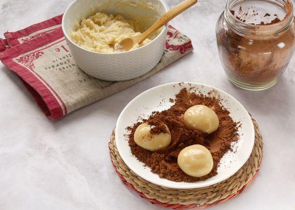 Заготовки для домашних конфет из сухого молока в тарелке с какао-порошком
