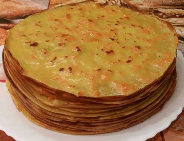 стопка морковных блинов на большой белой тарелке
