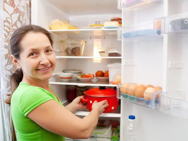 Женщина ставит горячую кастрюлю в холодильник