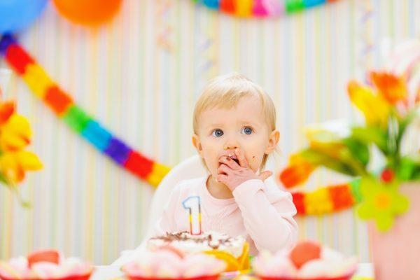 Годовалая девочка сидит перед именинным тортом