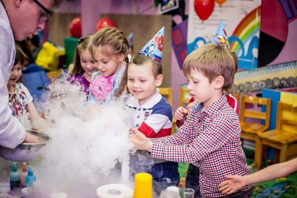 Взрослый демонстрирует детям химические опыты