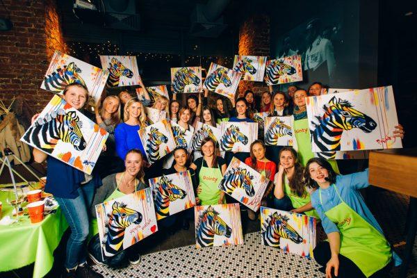 Участники пэйнти пати с картинами в руках
