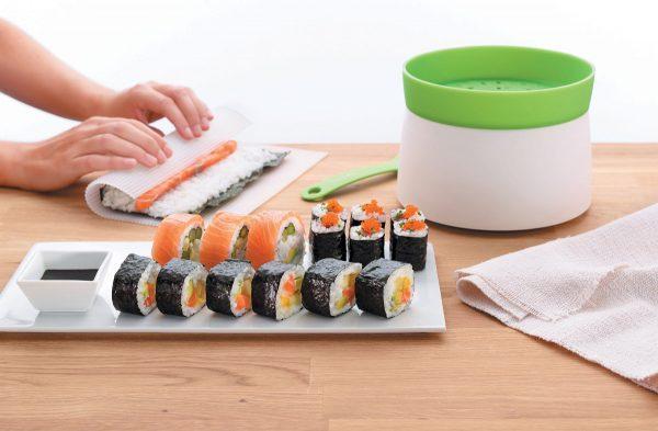 Женские руки крутят суши-роллы