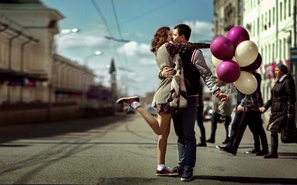 Влюблённая пара с воздушными шарами на городской улице