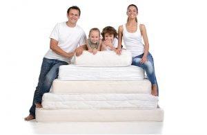 Счастливая семья на стопке матрасов