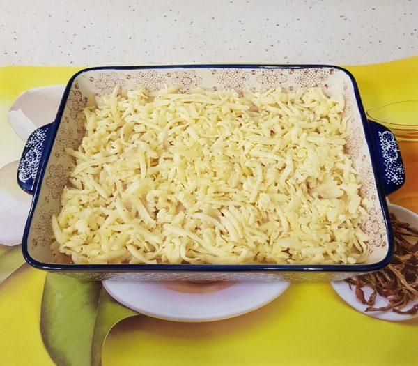 Слой тёртого сыра в прямоугольной форме с заготовкой для запеканки