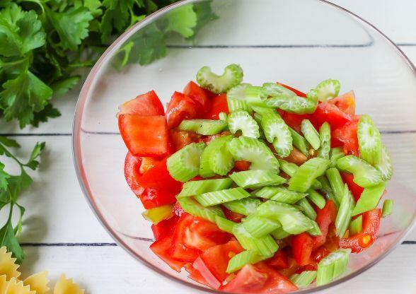 Нарезанные помидоры, болгарский перец и стебель сельдерея в стеклянной миске