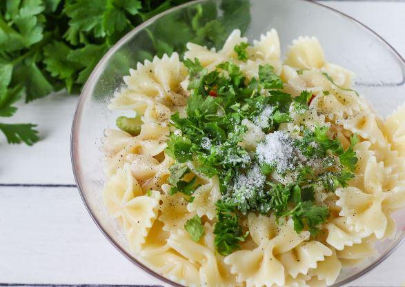 Отварные макароны, свежие овощи, зелень и специи в стеклянной миске