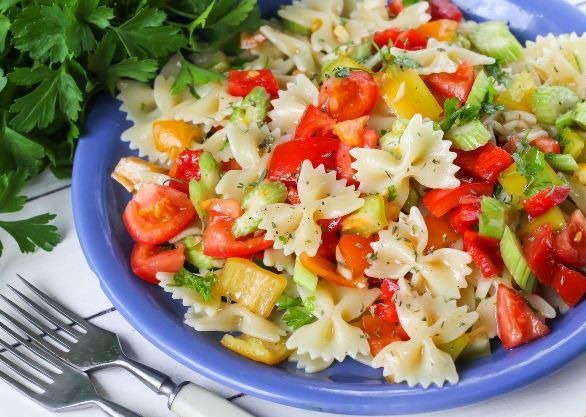 Салат из макарон и овощей в голубой ёмкости на столе