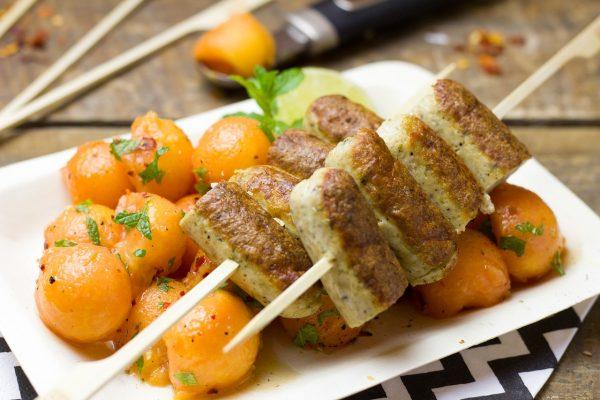 Мясные котлеты и гарнир из шариков папайи на тарелке
