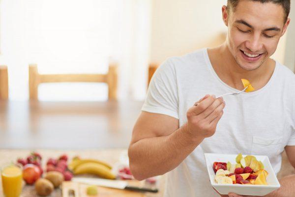 Мужчина ест салат из папайи и других фруктов