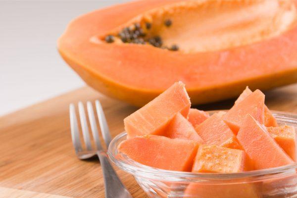 Вилка и кусочки папайи возле половинки фрукта