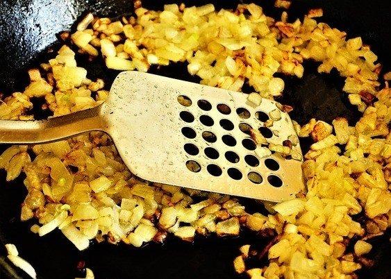 Обжаренный репчатый лук в сковороде с металлической лопаткой