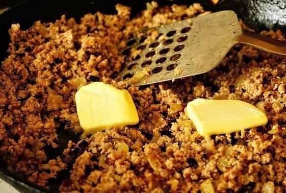 Кусочки сливочного масла в сковороде с мясным фаршем
