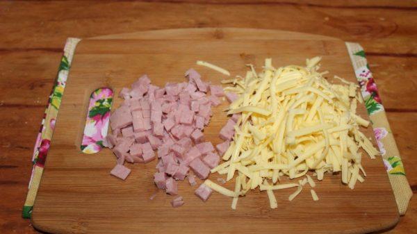 Нарезанная кубиками ветчина и тёртый твёрдый сыр на разделочной доске