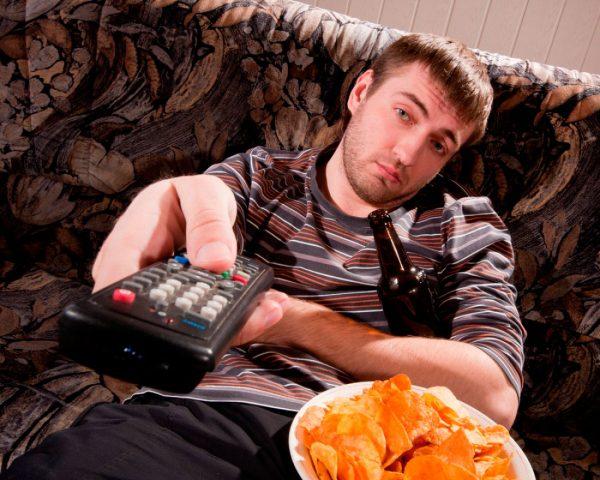 Мужчина сидит на диване и переключает каналы