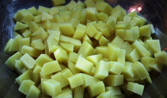 Нарезанный маленькими кубиками сырой картофель