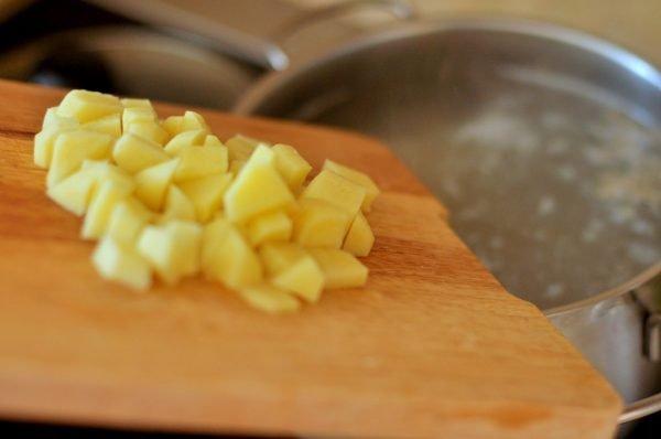 Нарезанный кубиками сырой картофель на разделочной доске