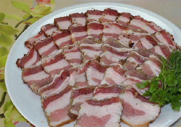 Тарелка с ломтиками солёного сала и веточкой свежей зелени