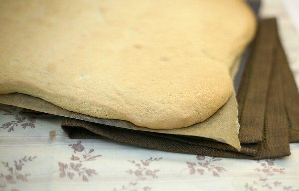 Пласт готового бисквита на противне с пекарской бумагой