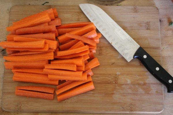 Нарезанная длинными полосками сырая морковь и нож на разделочной доске