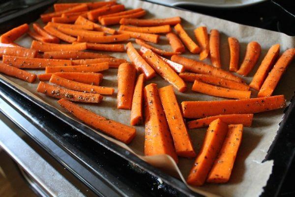 усочки моркови на противне с пекарской бумагой