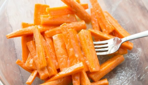 Кусочки моркови в растопленном сливочном масле и металлическая вилка