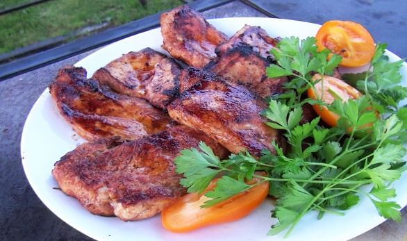 Отбивные из куриного филе с мёдом и горчицей на тарелке с овощами и зеленью