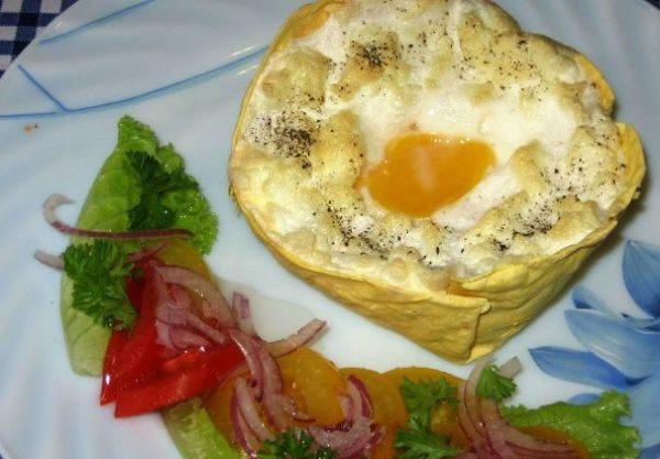 Готовая яичница «Орсини» на тарелке с овощным салатом