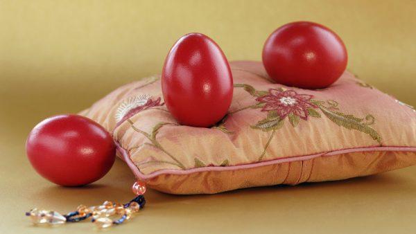 Три бордовых яйца на декоративной подушке