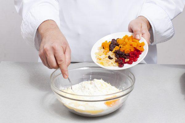 Мука и яичные желтки в стеклянной миске и смесь сухофруктов и цукатов в блюдце
