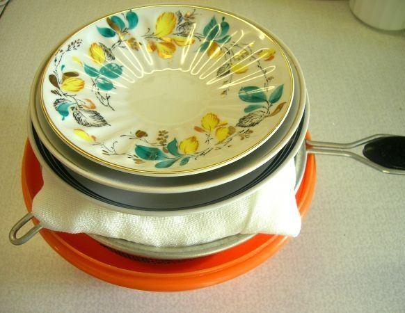 Творожная пасха в дуршлаге с марлей под стопкой фарфоровых блюдец