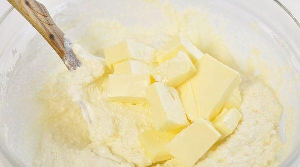 Кусочки сливочного масла в миске с творожной массой