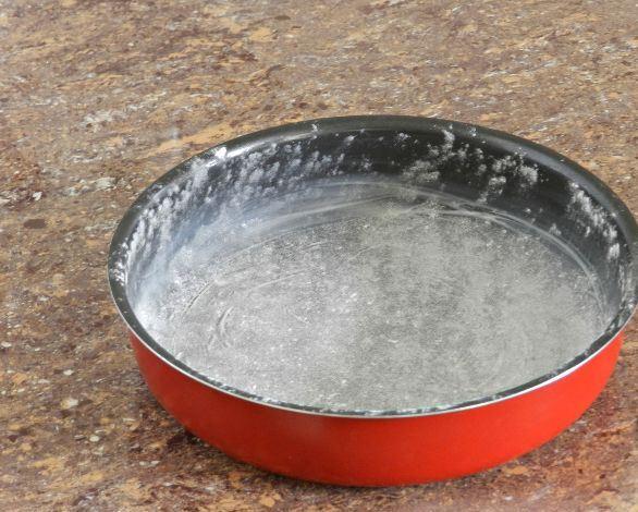 Круглая форма для выпекания, смазанная сливочным маслом и присыпанная мукой