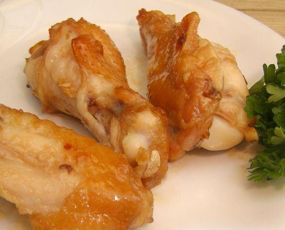 Запечённые в духовке куриные крылышки на тарелке с зеленью