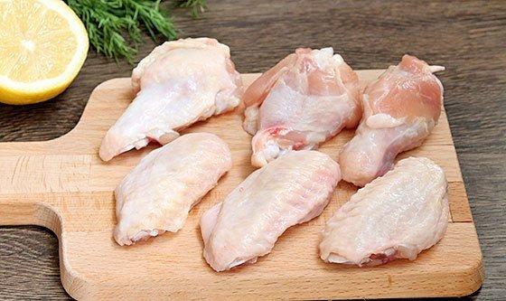 Кусочки куриных крылышек на деревянной разделочной доске