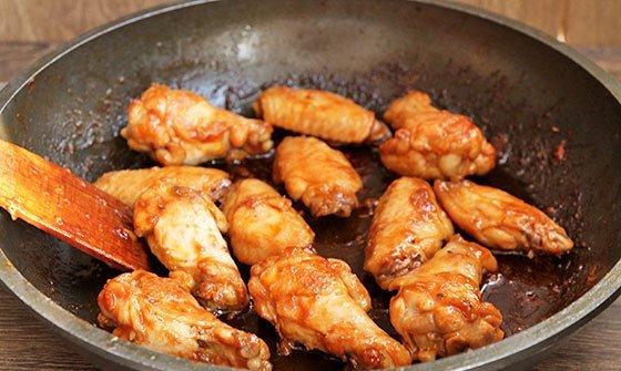 Готовые куриные крылья в медово-соевом соусе на сковороде с деревянной лопаткой