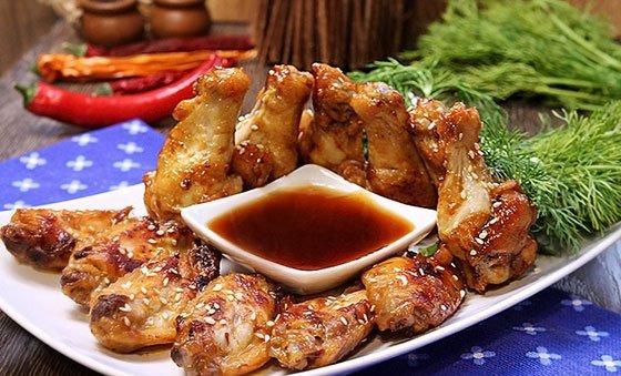 Жареные куриные крылья в медово-соевом соусе на тарелке