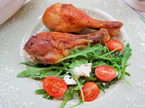 Куриные голени с румяной корочкой на тарелке с салатом из рукколы, черри и сыра