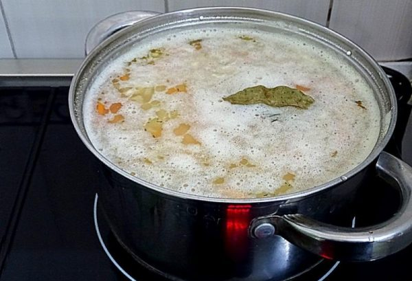 Кипящий суп на плите в большой кастрюле
