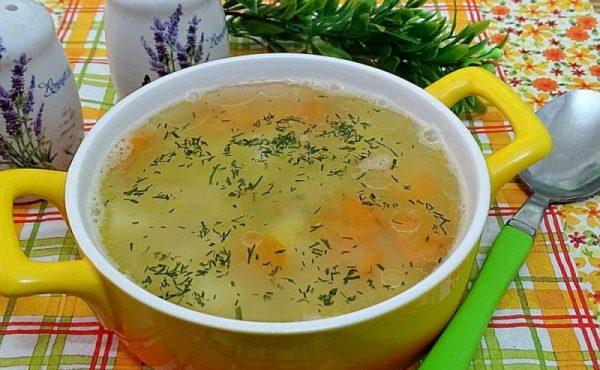 Гороховый суп без мяса со свежим рубленым укропом на столе с ложкой