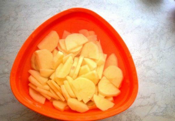 Нарезанный пластинками сырой картофель в красной пластиковой миске