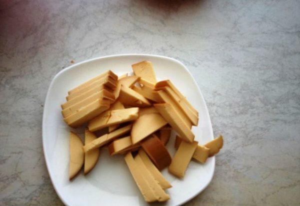 Нарезанный соломкой копчёный колбасный сыр на тарелке