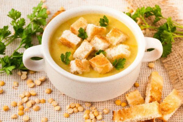 Гороховый суп с сухариками на столе с зеленью