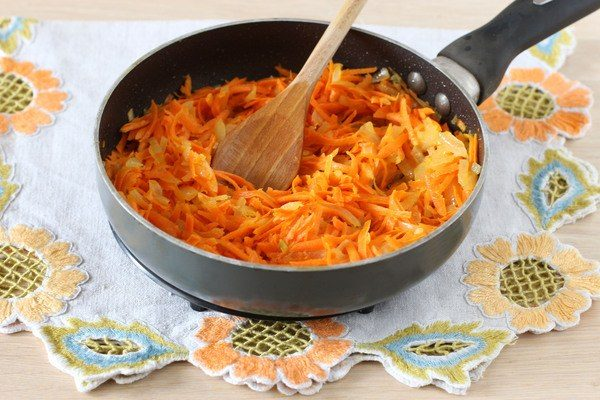 Зажарка из лука и моркови в сковороде на столе